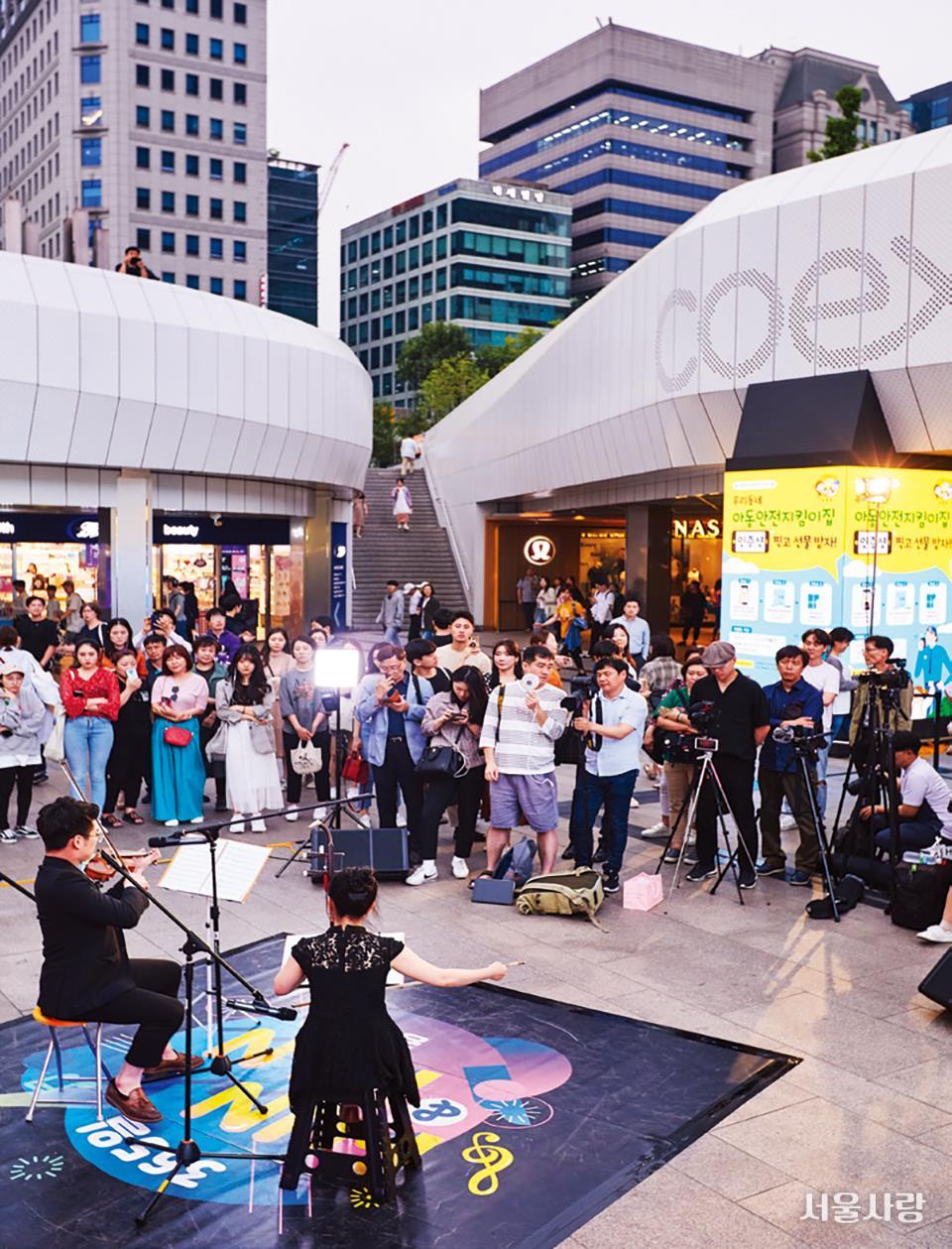 시민들이 코엑스 밀레니엄광장에서 진행되는 공연을 관람하고 있다.