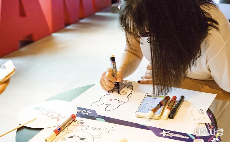 자신만의 스타일로 응원 카드를 완성하는 팬의 모습.