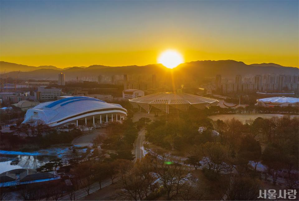 올림픽공원의 언덕에 서면 도심 너머 저 멀리 능선을 따라 붉고 둥근 태양이 얼굴을 삐죽이 내미는 모습을 볼 수 있다